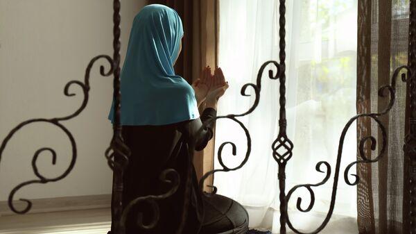 Молодая мусульманка во время молитвы