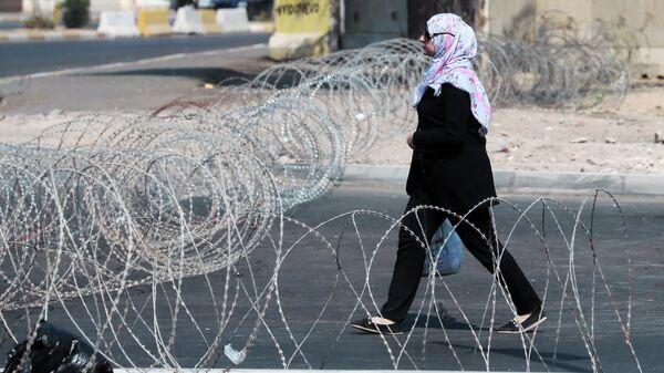 Девушка идет по улице Багдада, огражденной колючей проволокой