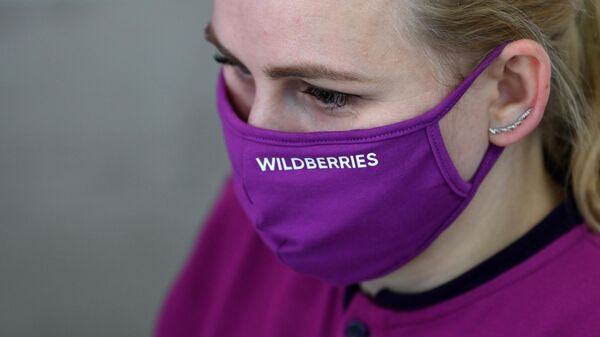 Сотрудник в защитной маске в пункте выдачи товара интернет магазина Wildberries в Москве