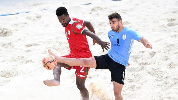 Слева направо: Абдулла Аль-Саути (Оман) и Андрес Лаэнс (Уругвай) в матче группового этапа чемпионата мира по пляжному футболу 2021 между сборными командами Уругвая и Омана.