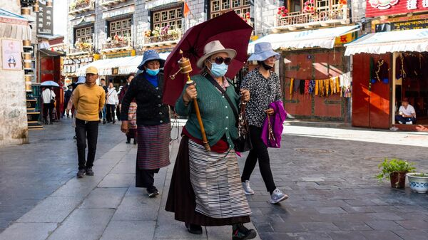 Местные жители на пешеходной улице Баркхор в центре города Лхаса в Тибете