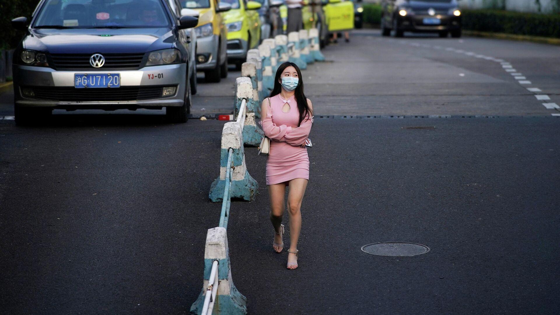 Женщина в защитной маске идет по улице в Шанхае, Китай - РИА Новости, 1920, 02.09.2021