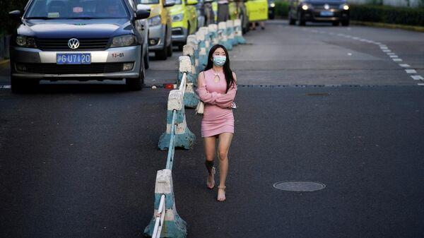Женщина в защитной маске идет по улице в Шанхае, Китай