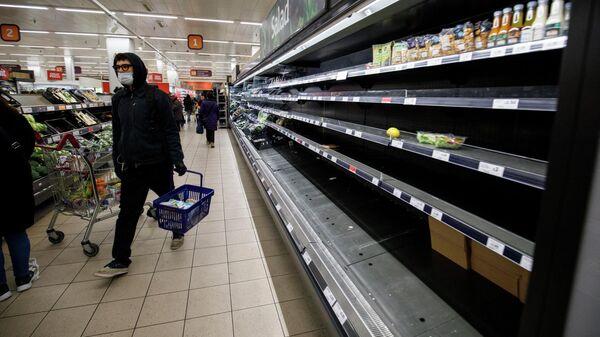 Люди возле пустых полок в супермаркете Лондона