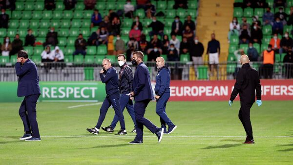 Moldova's Italian head coach Roberto Bordin (2R) walks on the pitch as the FIFA World Cup Qatar 2022 qualification football match between Moldova and Austria is delayed due to security reasons at Zimbru stadium in Chisinau on September 1, 2021. (Photo by Bogdan TUDOR / AFP)