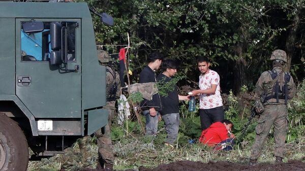 Польские пограничники и группа мигрантов, застрявших на границе между Беларусью и Польшей возле села Уснарж-Горный, Польша