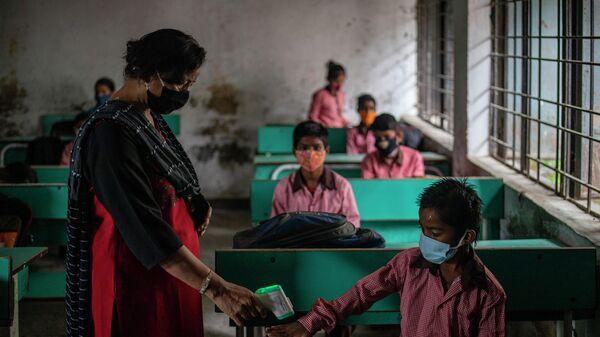 Учитель проверяет температуру тела ученика в первый день частичного открытия школ в Ноиде, пригороде Нью-Дели, Индия