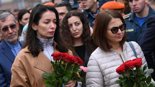 Женщины с цветами во время церемонии возложения цветов и венков к памятнику жертвам террористического акта в Беслане перед Храмом Рождества Пресвятой Богородицы на Кулишках в Москве
