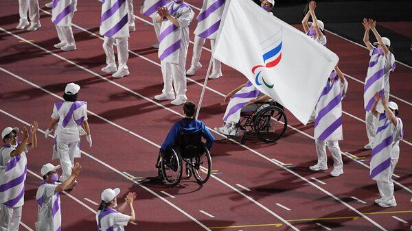 Знаменосец команды Паралимпийского комитета России (команда ПКР), пловец Роман Жданов во время торжественной церемонии закрытия XVI летних Паралимпийских игр в Токио на Национальном олимпийском стадионе.