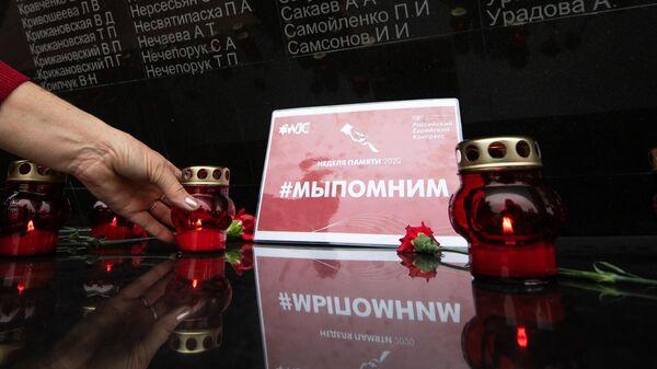 Цветы и свечи у стены скорби на территории Мемориала жертвам фашистской оккупации Крыма 1941-1944 гг. Концлагерь Красный