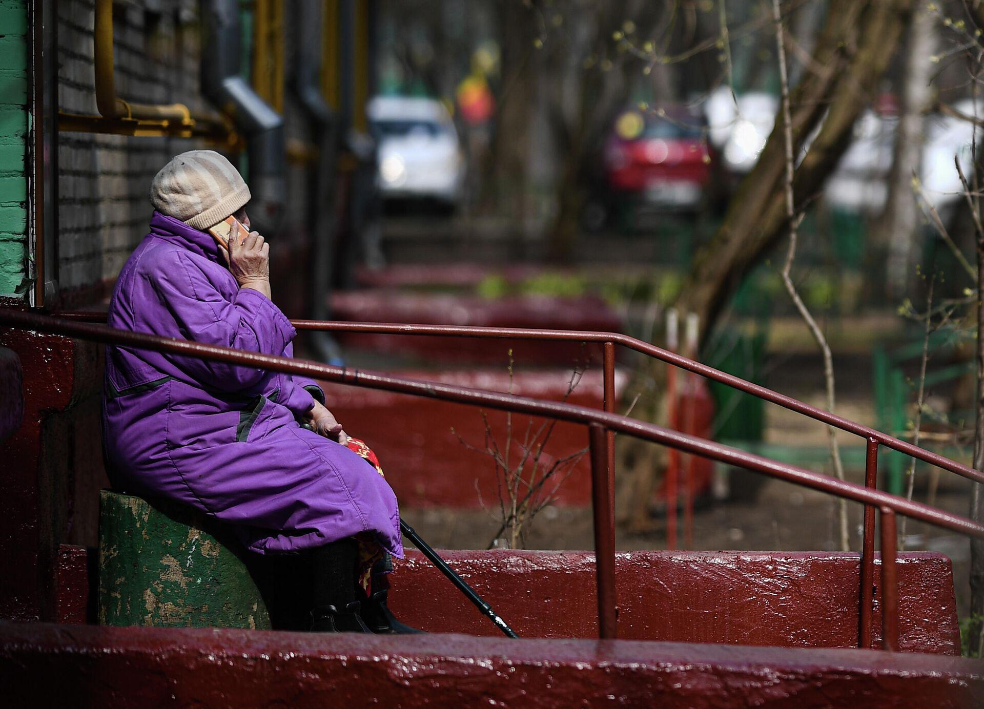 Пожилая женщина разговаривает по мобильному телефону у подъезда своего дома - РИА Новости, 1920, 08.09.2021