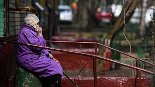 Пожилая женщина разговаривает по мобильному телефону у подъезда своего дома