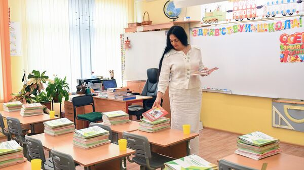 Учитель раскладывает тетради в классе