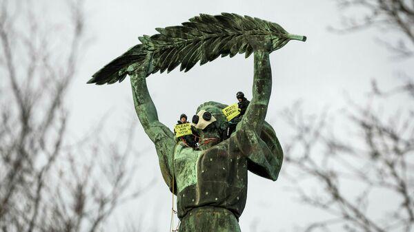 Экологические активисты Гринпис проводят демонстрацию против загрязнения воздуха на статуе Свободы в Будапеште, Венгрия.