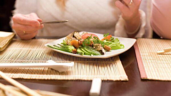 Женщина ест салат в японском ресторане