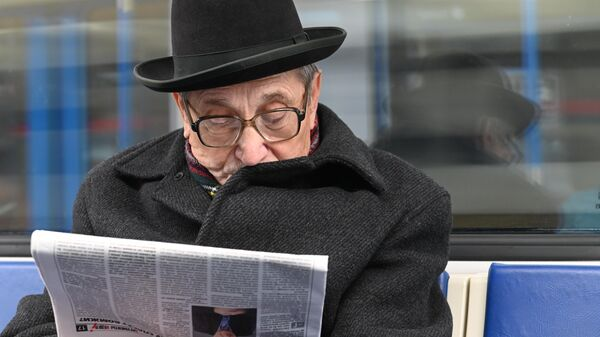 Мужчина читает газету во время поездки в метро