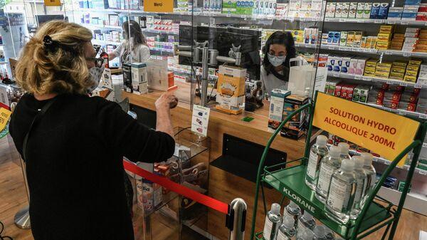 Женщина покупает лекарства в аптеке в Пероле, южная Франция