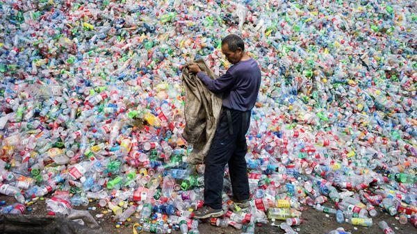 Китайский рабочий, сортирующий пластиковые бутылки для переработки, на окраине Пекина