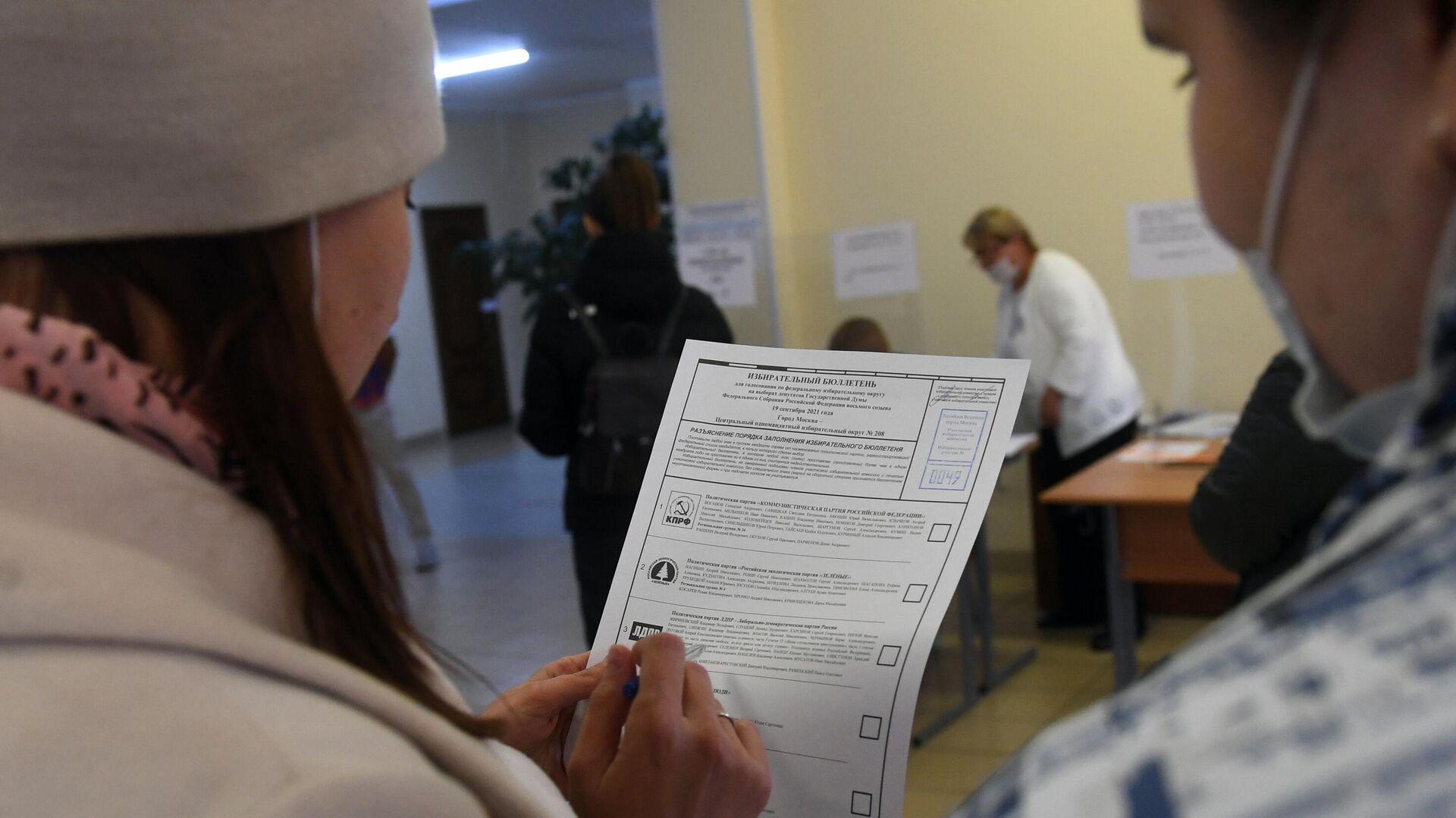 Девушки во время голосования на выборах в Госдуму на избирательном участке №49 в Москве - РИА Новости, 1920, 17.09.2021