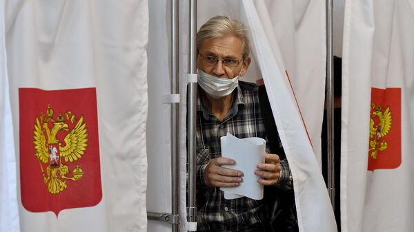 Мужчина голосует на избирательном участке в Симферополе