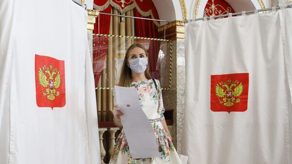 Девушка голосует на избирательном участке №20-10 в Краснодаре