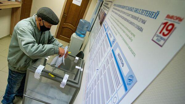 Мужчина голосует на выборах депутатов Государственной Думы РФ на избирательном участке №8180 в консульском отделе посольства России в Латвии