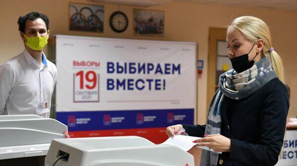 Девушка голосует на избирательном участке в Москве