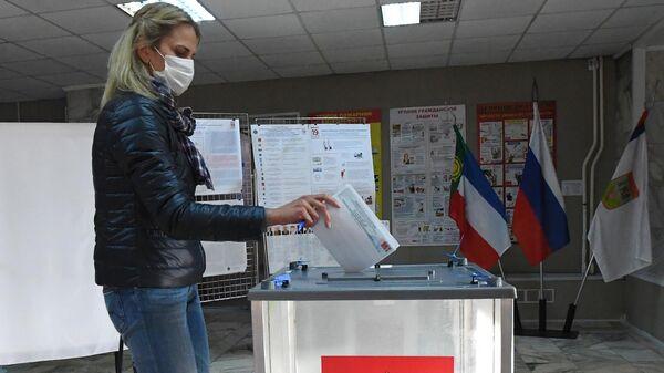 Женщина голосует на избирательном участке №33 на выборах депутатов Государственной Думы РФ в Республике Хакасия