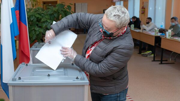 Женщина голосует на выборах депутатов Государственной Думы РФ на избирательном участке №51 на выборах в Госдуму в Петропавловске-Камчатском
