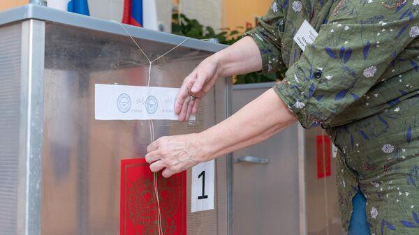 Сотрудник участковой избирательной комиссии №51 в городе Петропавловске-Камчатском пломбирует стационарные урны для голосования