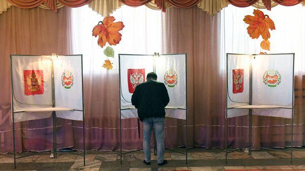 Избиратель голосует на избирательном участке №254 на выборах депутатов Государственной Думы РФ в районном Доме культуры села Бея в Республике Хакасия