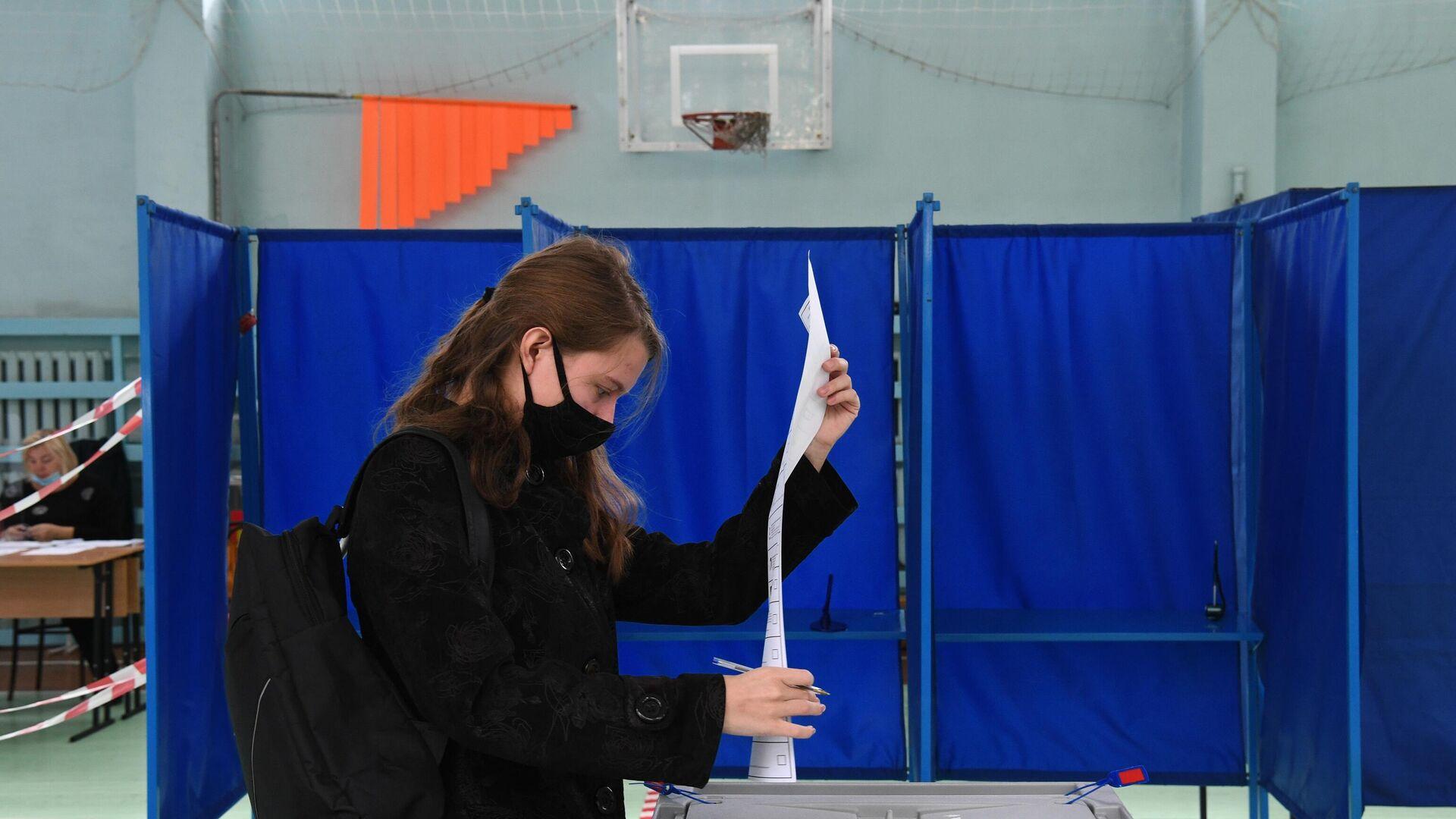 Девушка во время голосования на избирательном участке в Новосибирске - РИА Новости, 1920, 19.09.2021