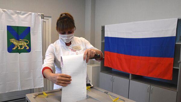 Медицинский работник принимает участие в голосовании на избирательном участке в Приморском краевом перинатальном центре (ГБУЗ ПКПЦ) во Владивостоке