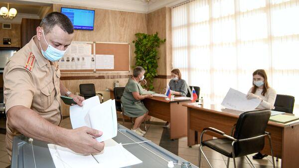 Мужчина голосует на выборах депутатов Государственной Думы Федерального собрания Российской Федерации VIII созыва на избирательном участке № 8017 в Баку