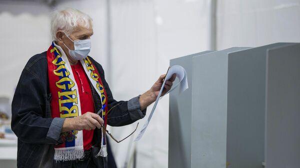 Мужчина голосует на выборах депутатов Государственной Думы РФ на избирательном участке №8159 в посольстве России в Киргизии