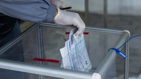 Избиратель голосует на выборах депутатов Государственной Думы РФ на избирательном участке №8159 в посольстве России в Киргизии