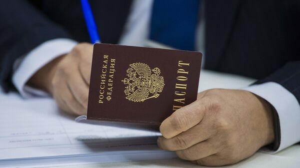 Сотрудник избирательной комиссии на участке №8159 в посольстве России в Киргизии вносит сведения из паспорта гражданина РФ