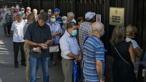 Люди стоят в очереди у входа на избирательный участок №8159 в посольстве России в Киргизии, чтобы проголосовать на выборах депутатов Государственной Думы РФ