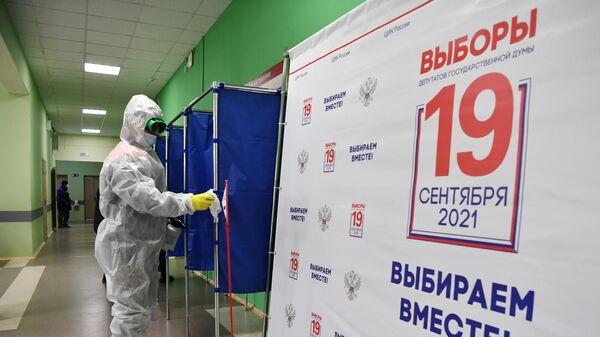 Дезинфекция кабинок на избирательном участке, где проходит голосование на выборах депутатов Государственной Думы РФ