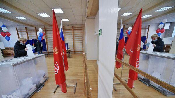 Избиратель голосует на участке в Санкт-Петербурге на выборах депутатов Государственной Думы РФ