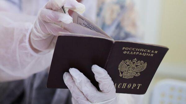 Сотрудница избирательного участка смотрит паспорт избирателя перед выдачей бюллетеня для голосования на выборах депутатов Государственной Думы РФ