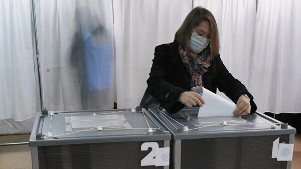 Избирательница опускает бюллетень в урну для голосования на избирательном участке в Красноярском крае