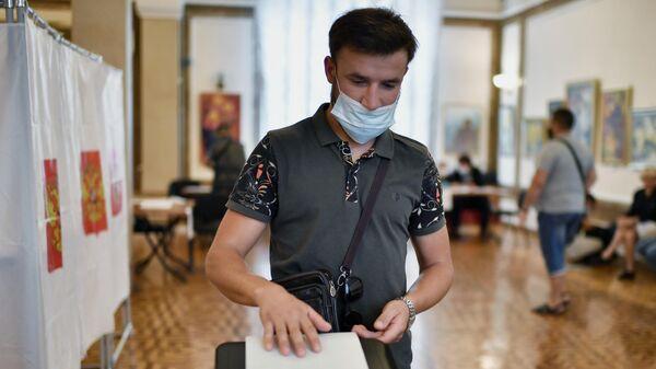 Избиратель на участке во время голосования на выборах депутатов Государственной Думы РФ в Севастополе