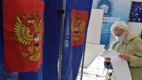 Избиратель голосует на выборах депутатов Государственной Думы РФ на участке в Санкт-Петербурге