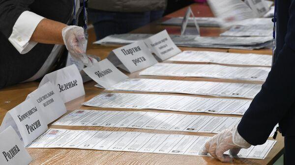 Сортировка бюллетеней во время подсчета голосов после закрытия избирательного участка в Новосибирске
