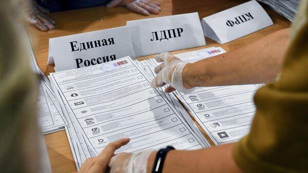 Сортировка бюллетеней во время подсчета голосов после закрытия избирательного участка №1986 в Новосибирске