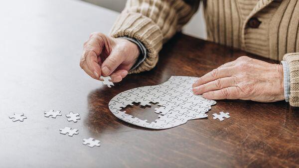 Человек с болезнью Альцгеймера собирает пазл