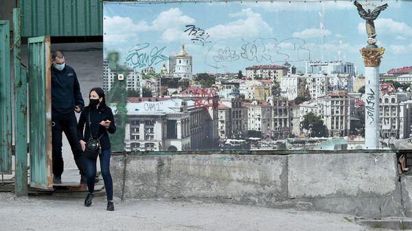 Люди в масках проходят мимо баннера с изображением Киева