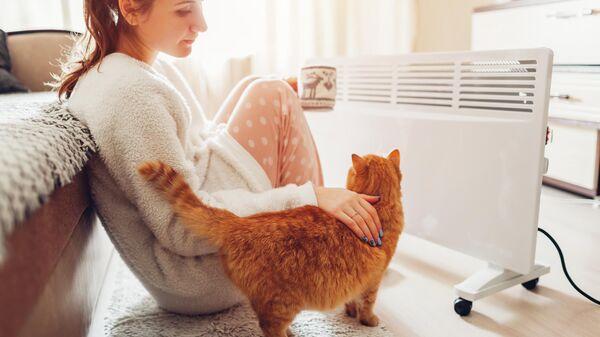 Девушка с котом у обогревателя