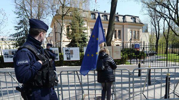 Полицейские и женщина с флагом ЕС у здания Конституционного суда в Варшаве